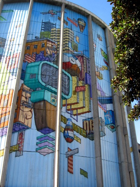 Moving around toward the brightly sunlit east side and 8th Avenue. The high mural is viewed beyond some trees.