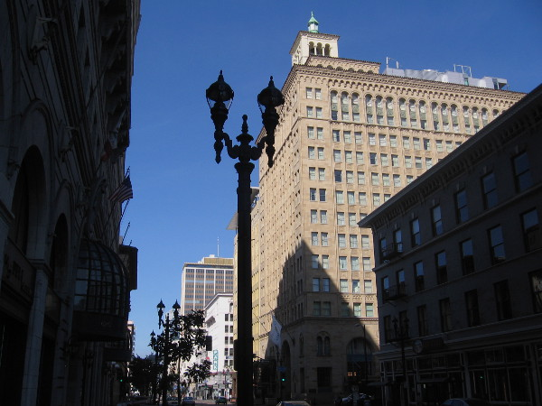 Photo of the San Diego Trust and Savings Bank Building taken from one block east on Broadway. The 14-story structure is topped with a two-story penthouse and cupola.