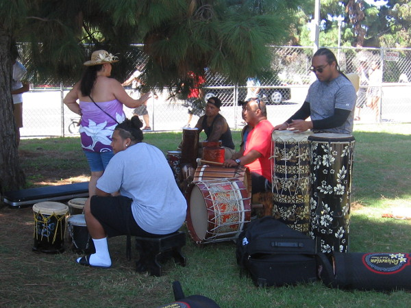 Drummers create rhythmic beats for event performers rehearsing behind the stage under some shady trees.