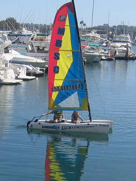 A colorful sail and reflection on smooth water at the Hyatt Regency Mission Bay Marina.