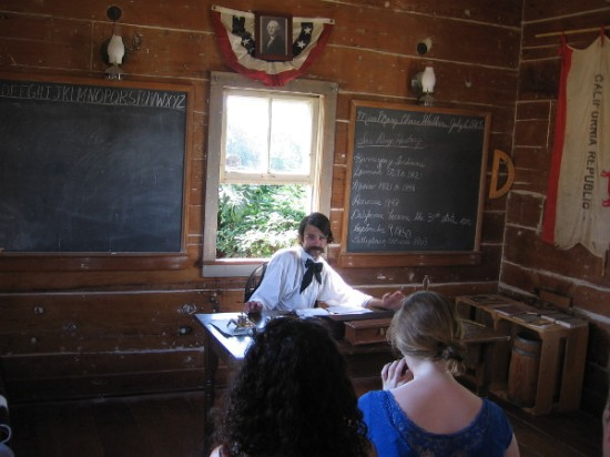 Gentleman in period attire tells visitors at Old Town San Diego State Historic Park about the history of the Mason Street School.