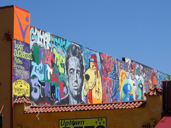 This is the best photo I could get of a really long colorful mural along a rooftop. I see James Dean and Muttley!