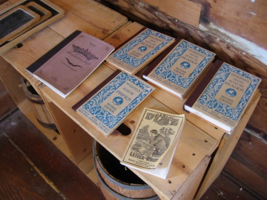 Some old Primers and Readers on a wooden table. A water bucket and dipper were used for drink.