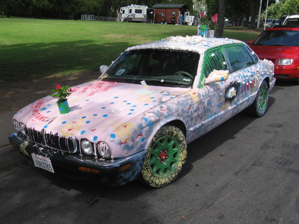 A delightfully painted car topped with flower pots!
