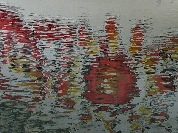 Orange and yellow logo of visiting Norwegian Sun cruise ship reflected on rippled water in San Diego Bay.