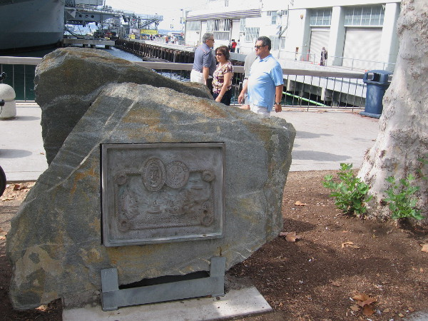 People pass the Navy Bicentennial Commemorative Plaque, displayed on San Diego's Embarcadero, on the Greatest Generation Walk near the USS Midway Museum. Photo taken October 17, 2015.