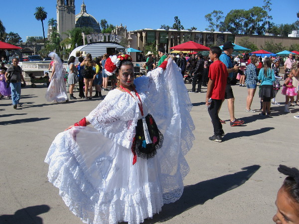 A lady, with a skull face painting, poses in a beautiful Dia de los Muertos dress. What could possibly go wrong today?