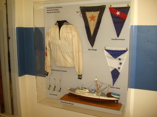 Display case contains artifacts from the San Diego Maritime Museum, including model of a tuna boat.