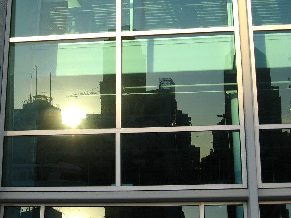 Reflection of downtown San Diego's nearby skyline in the windows of the Port Pavilion. Photo taken as the sun climbs above building rooftops, from the Broadway Pier.