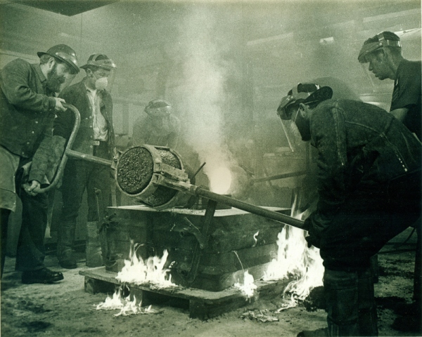 Molten bronze is poured in the foundry of the USS Ajax. Historical photograph of the Navy Bicentennial Commemorative Plaque being created. Photo credit: United States Navy.