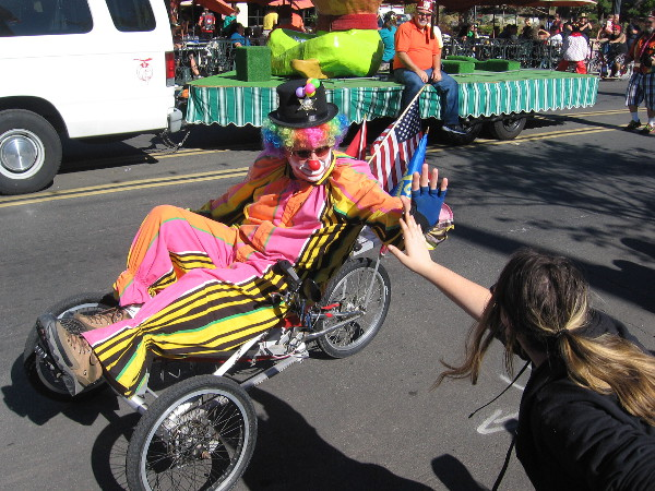 Shriner clown gives high fives to crowd during the 2015 Mother Goose Parade in El Cajon, California.