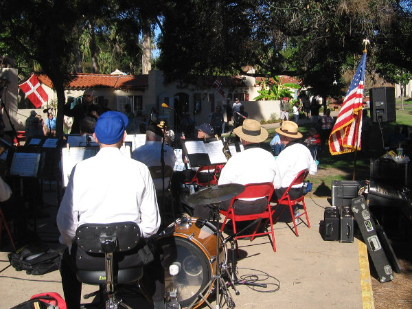 The band is ready to play as people gather around the stage in the lawn area of the International Cottages. It's a Sunday afternoon in San Diego's beautiful Balboa Park.