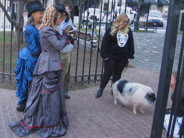 Ladies in frilly dresses linger between television shoots promoting San Diego's Fall Back Festival. The event, located near the William Heath Davis House Museum, will recreate a 1880s frontier town.