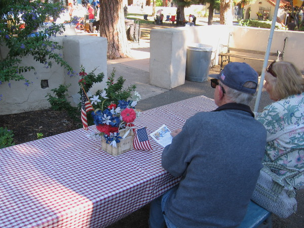 Folks at a table in front of the House of USA Cottage listen to the band play patriotic and other popular tunes.