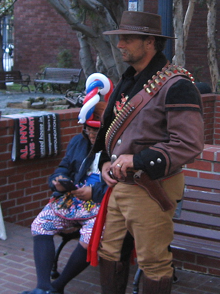 A tough Western character hangs out with a silly balloon twister guy. The bench is outside the William Heath Davis House in the Gaslamp.
