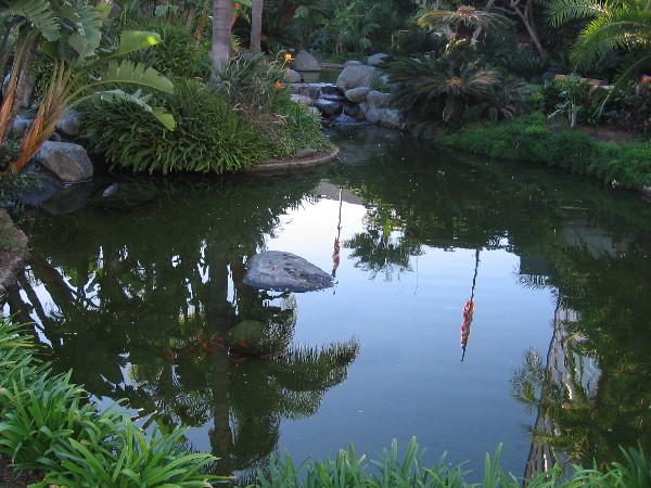 A shining pond reflects the nearby hotel and flagpoles on another perfect San Diego day.