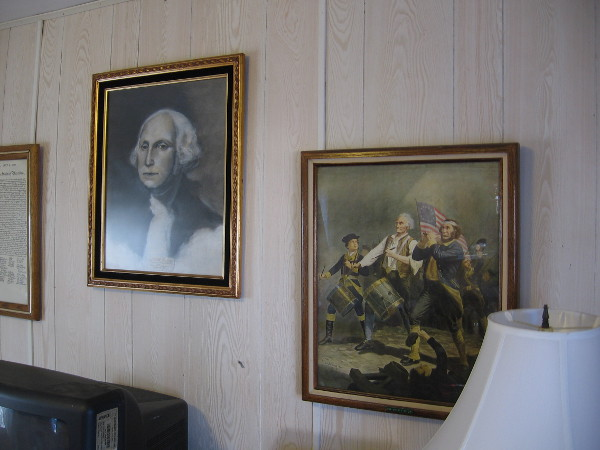 Famous portraits and memorabilia from American history cover walls and fill shelves in the House of USA Cottage.