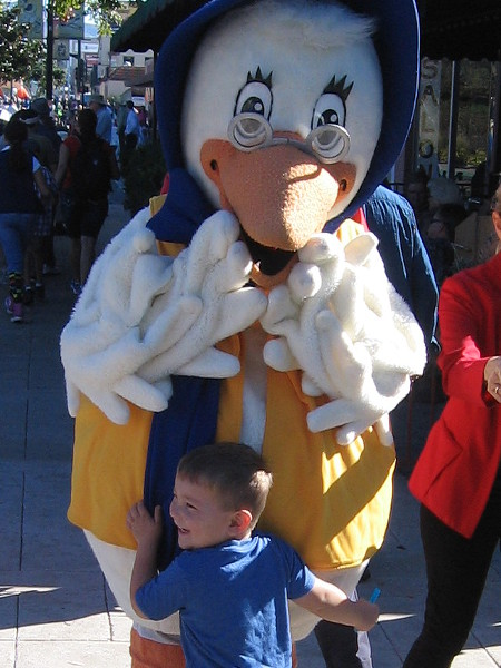 A young boy hugs Mother Goose before the parade begins.