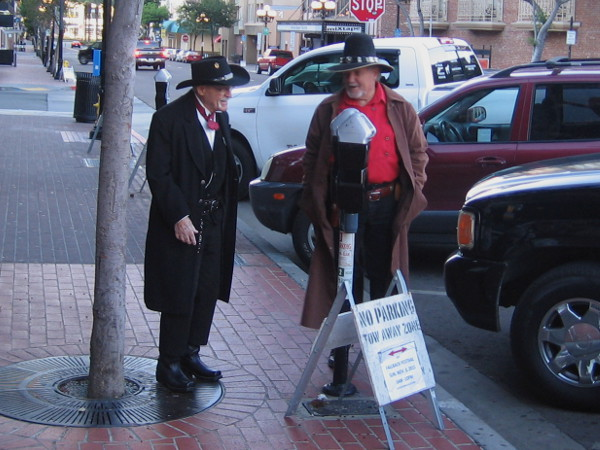 Two gentleman from the Old West converse on Fourth Avenue in San Diego's modern Gaslamp Quarter.