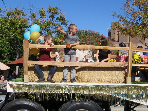Kids wave from a float dedicated to raising awareness about childhood cancer.