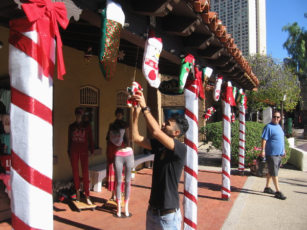 Jolly old Saint Nick is being hung with care near stockings and candy cane pillars at the front door of a Seaport Village shop.