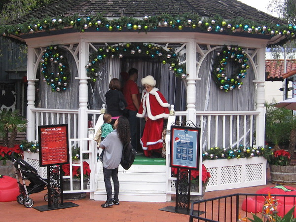 Mrs. Claus greets a child and mother at the Seaport Village's East Plaza Gazebo.