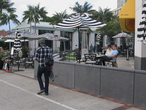 A guy carrying a skateboard ambles past outdoor diners at Sally's Seafood on the Water.