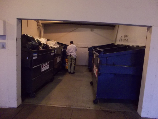 A building's dumpsters are ready to be hauled out and emptied.