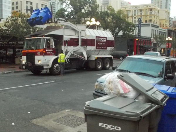 Blue recycle bins are lifted, banging and clattering, and contents are dumped.