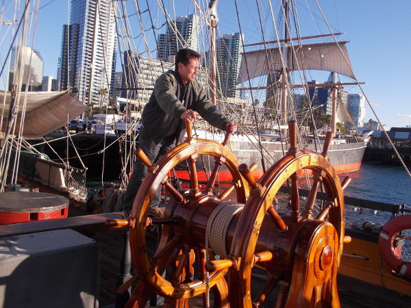 Visitor to the San Diego Maritime Museum pretends to steer the amazing tall ship, which is docked on the Embarcadero near the historic Star of India, in the background.