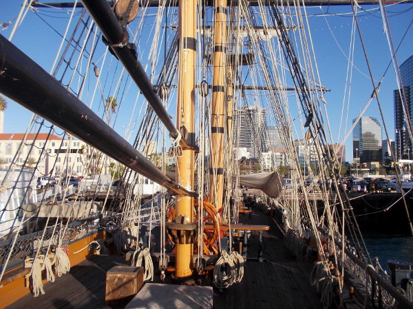 View of the ship's main deck and lower rigging from the quarterdeck. A portion of San Diego's skyline and the County Administration Building are visible.