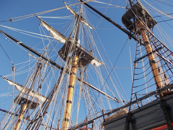 Looking upward at the three masts, furled sails and other complicated rigging.