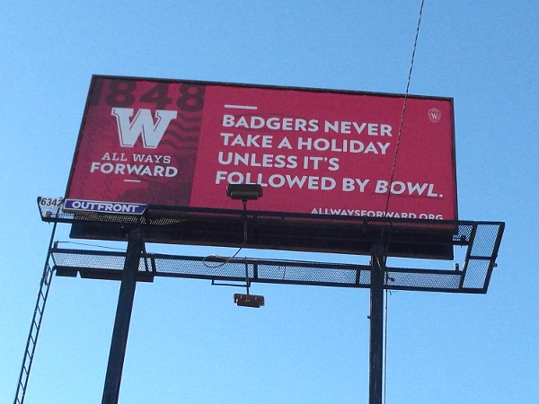Opposite side of the same billboard proudly reads BADGERS NEVER TAKE A HOLIDAY UNLESS IT'S FOLLOWED BY A BOWL.