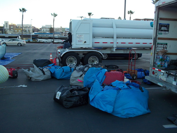 A truck hauling helium, and numerous big balloon wait ready to be filled.