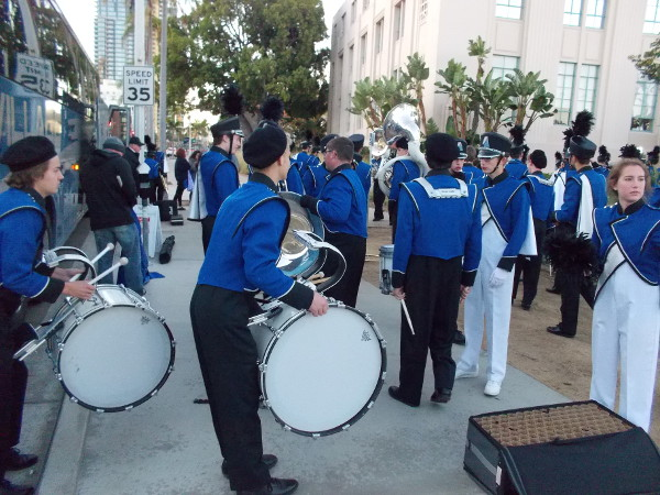 Band members get off the bus with instruments.