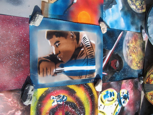 Finn, heroic character in Star Wars: The Force Awakens, holds a lightsaber. Cool spray paint art by William J. Dorsett.