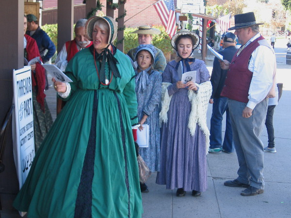A group of old-fashioned Christmas carolers in Victorian costumes brings holiday cheer to Old Town San Diego State Historic Park.