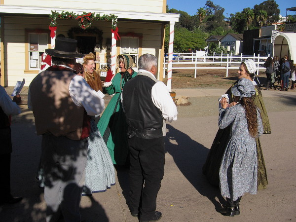 Carolers smile, laugh and enjoy the day in front of a reconstructed building at Old Town San Diego's central plaza.