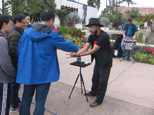 Tourists are shown magic by a fun busker near the reflecting pond in Balboa Park.