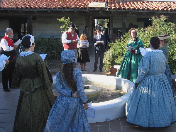 Singing traditional Christmas carols around the old fountain in the outdoor courtyard of Casa de Estudillo.