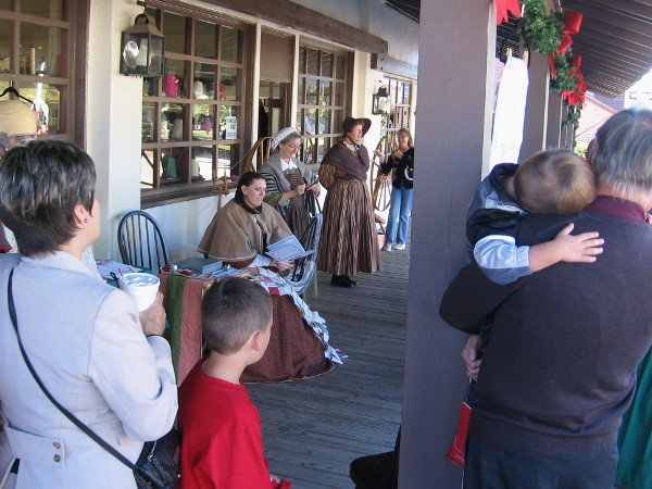 A crowd gathered as Christmas carols were heard outside the Threads of the Past Living History Activity Center. One quilter joined in the public singing!
