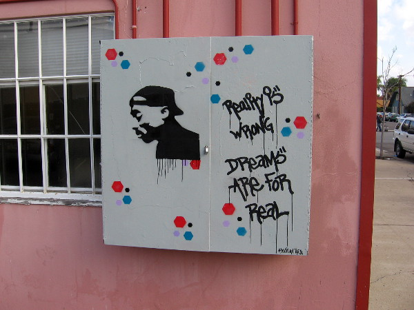This street art is on the same building. It reads Reality is Wrong. Dreams are for Real. Hooligan Arts.