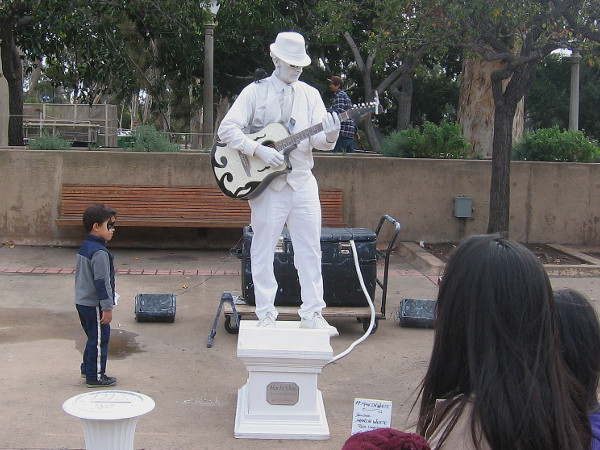 Kid with painted face examines Man in White. This cool busker appears to be made of marble. He was entertaining surprised visitors on El Prado.