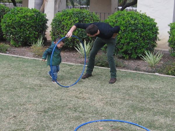 Kid walks through a hula hoop on a stretch of grass.