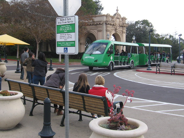Folks wait on a bench for the free Balboa Park tram, which I call the green caterpillar.