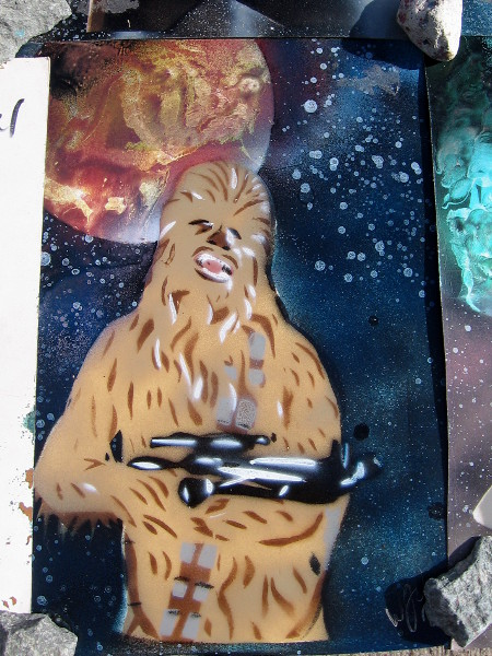 It's Chewbacca with his Bowcaster blaster under a distant galaxy's stars and a colorful planet.