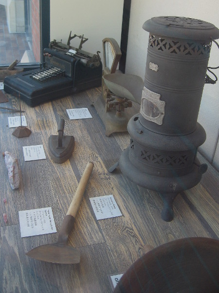 Items from daily life in old Chinatown include kerosene heater, iron, scale and soup spoon.