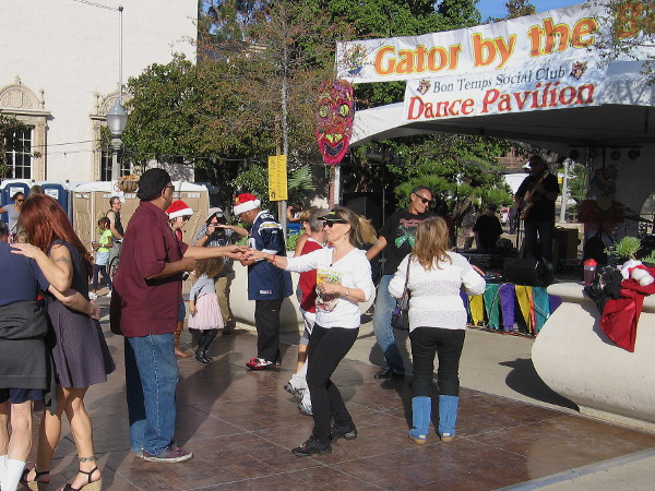 Folks in Santa hats enjoy dancing at the Gator by the Bay stage in the Plaza de Panama.