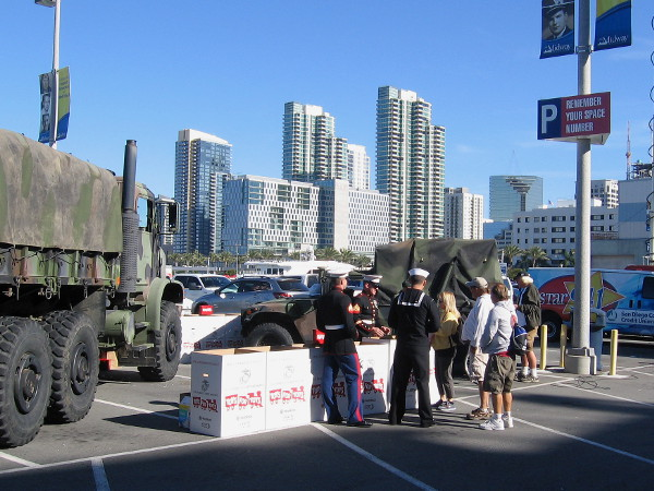 Marines collect toys to help spread holiday cheer, with downtown San Diego's skyline in the background.