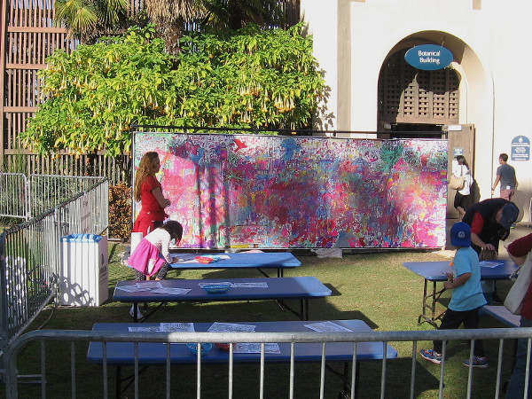 Kids by the Botanical Building paint a huge community canvas during December Nights.